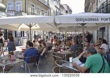 PORTO, PORTUGAL - AUGUST 19, 2016: People eating outdoor in an animated street in the historical center of Porto Portugal.