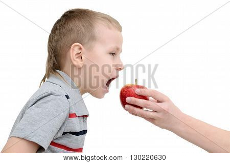 Boy eats an apple on a white background