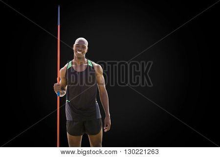 Front view of happy sportsman is holding a javelin