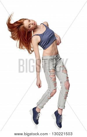 Modern red haired hip-hop style teenage girl jumping dancing isolated on a white background