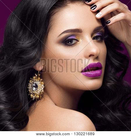 Beautiful brunette model with curls, classic makeup, gold jewelry and purple lips. The beauty of the face. Portrait shot in the studio.