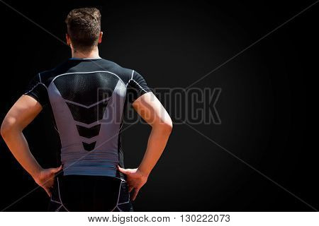 Rear view of sportsman posing with hands on hips