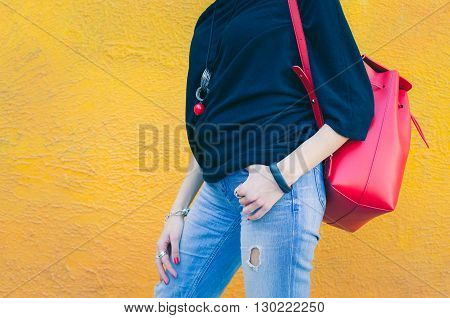 Fashionable beautiful big red backpack on the arm of the girl in a fashionable jeans, posing near the yellow wall on a warm summer night. Warm color