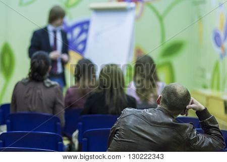 Male Professional Lecturer Speaking In front of the People. Horizontal Image Composition. Horizontal Image Composition