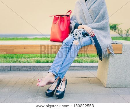 Girl in jeans took off her fashionable high-heeled shoes is resting sitting warm summer evening on the bench in the european city. Holiday. Shopping. Tiredness.