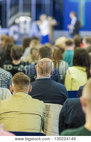 Business Conferences Concepts and Ideas. Two Hosts Speaking In front of the Large Group of People. Vertical Image
