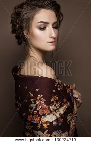 Beautiful girl in a shawl with a braid. Beauty face