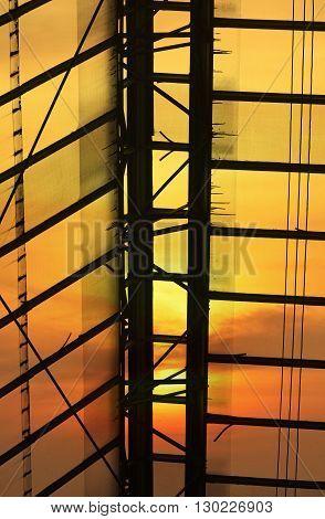 Green glass roof detail of Bangkok train station over sunset sky