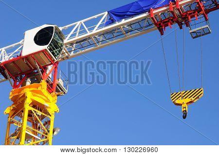 Assembled construction crane against blue cloudless sky.
