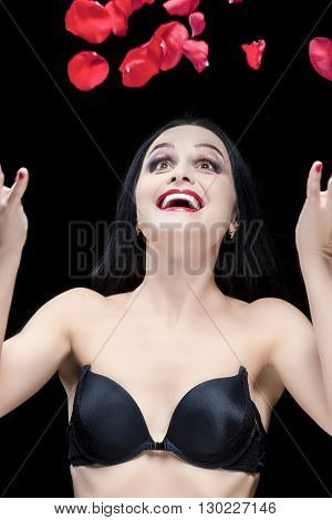 Sexy Looking Caucasian Brunette Woman With Flying Rose Petals Against Black. Vertical Image Composition