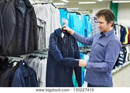 Handsome man chooses jacket in the supermarket