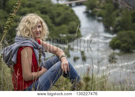 Beautiful girl is seating and relaxing on the hill of KRKA National Park with a panoramic view on the river