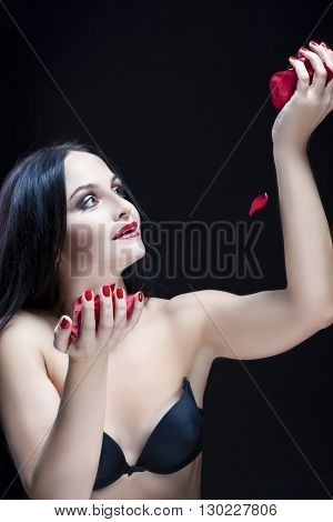 Brunette Woman in Lingerie Playing With Rose Leaves. Against Black. Vertical Image