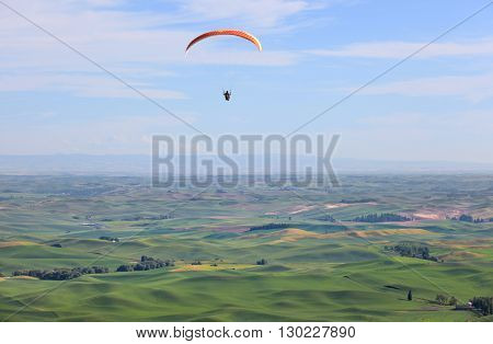 Para glider up in the sky above rolling hills of Palouse in Washington state.