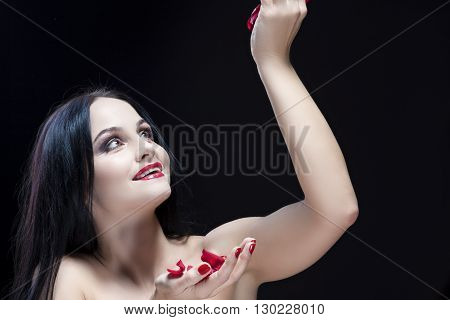 Brunette Woman in Lingerie Playing With Rose Leaves. Against Black. Horizontal Image Composition