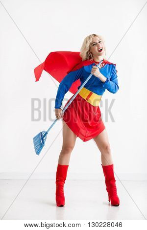 Beautiful super woman sweeping floor with a broom