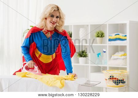 Attractive smiling superwoman ironing her casual clothes