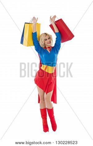 Happy excited superwoman raising with shopping bags