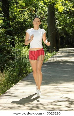 Young woman running outdoors in green park on sunny summer day