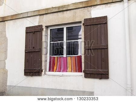 Window shutters and café curtains in French street