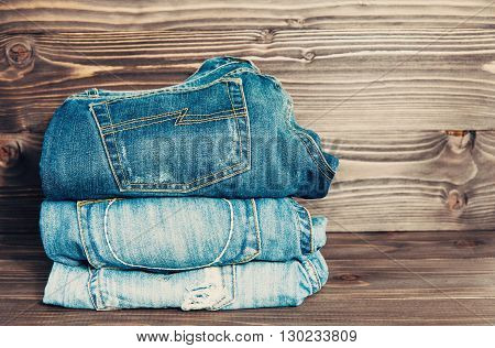 jeans stacked on a dark wooden background, vintage toned