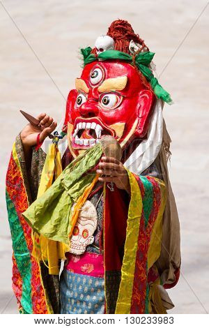 Unidentified monk with phurpa (ritual knife) performs a religious masked and costumed mystery dance of Tibetan Buddhism during the Cham Dance Festival in Hemis monastery, India.