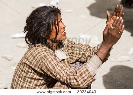 Hemis,India - June 29, 2012: homeless beggar women with outstretched arms asking for alms from visitors of the Cham Dance Festival of Tibetan buddhism in Hemis monastery, India.