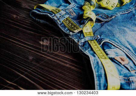 jeans and centimeter on a wooden background close up, toned