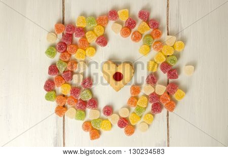 A circle formed by many vibrant gum drops with a heart-shaped tea cookie in the middle shot from above on a light wooden board texture with copyspace