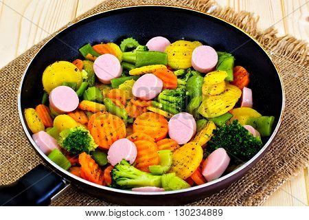 Steamed Vegetables Potatoes, Carrots and Broccoli with Sausages in a Pan Studio Photo
