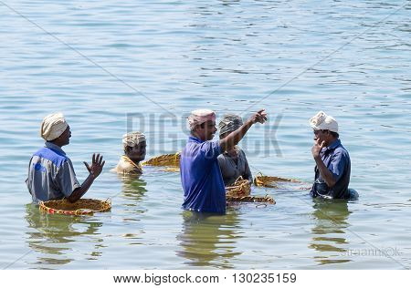 Vizhinjan, India - Jan 24, 2012: Group of lively conversating Indians waist deep in water in the fishing harbor of the Arabian Sea in anticipation of the return of fishermen with a catch in Vizhinjam Fishing Harbour, Kerala, Southern India.