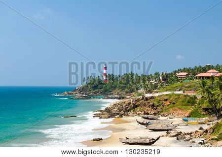 The lighthouse on the cape stretching into the Arabian Sea beach and fishing boats at a resort in Kerala in sunny weather