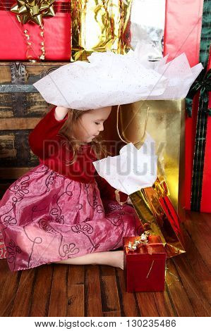 Little girl in a dress opening christmas gifts
