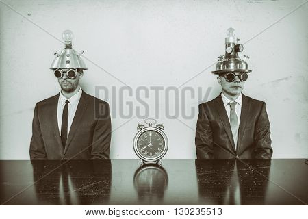 Two vintage businessman sitting at office desk with clock