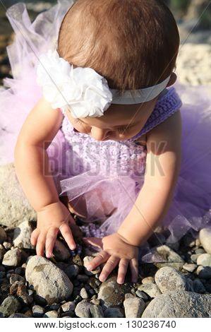 Beautiful brunette baby girl sitting on pebble beach