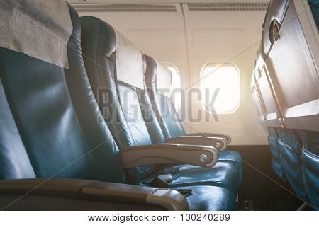 Empty aircraft seats and windows with sun light.