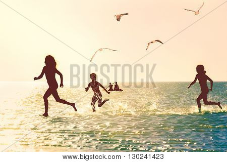 Silhouettes of children running through the water in the sea at sunset backlit. Photo toned