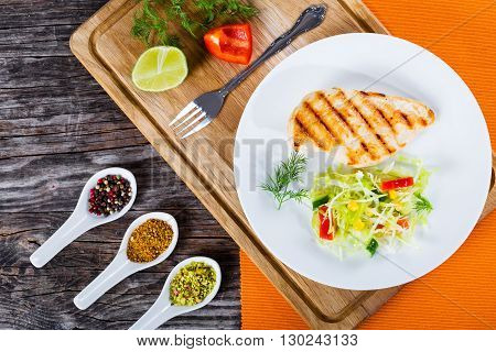 Healthy grilled chicken breast fillet with strip low calories spring cabbage salad with bell pepper corn and dill close-up studio light top view