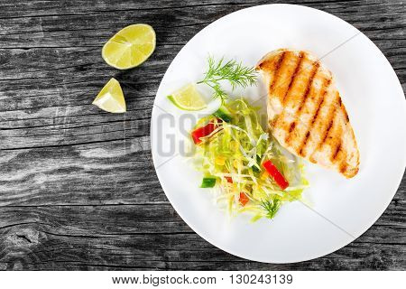 Healthy grilled chicken breast fillet with vegetables salad on a white dish on a wooden background blank space left studio light top view