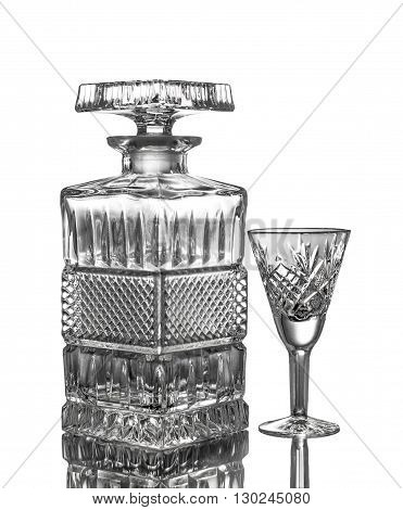 Crystal decanter and a glass. Isolated on white background with reflection.