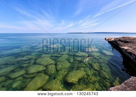 Lake Superior Rocky Coast - A girl swims in the pure water of Lake Superior in the Upper Peninsula of Michigan