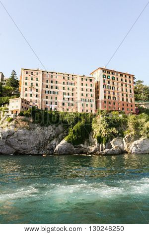 Apartment buildings on a steep rocky shore of the warm sea.