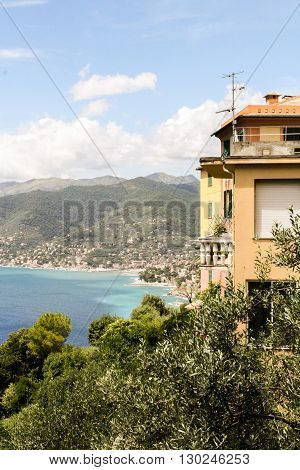 Ligurian coast - the mountains villages and beaches. In the foreground - the yellow house and garden.