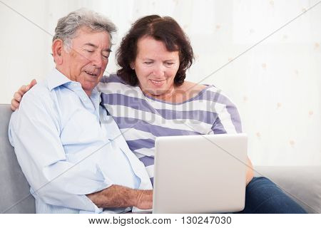 Daughter and father laughing while using laptop