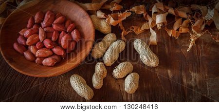peanuts in a wooden plate , wooden plate with peanuts on a stump