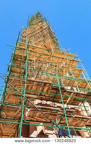 The spire of the Catholic Church in scaffolding against the blue sky