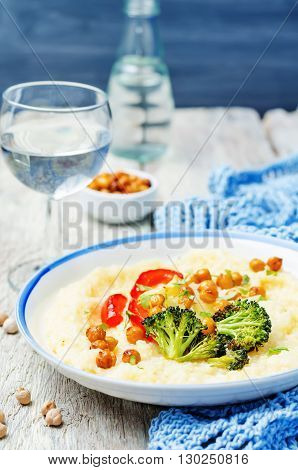 Polenta with roasted vegetables and chickpeas on a white wood background.