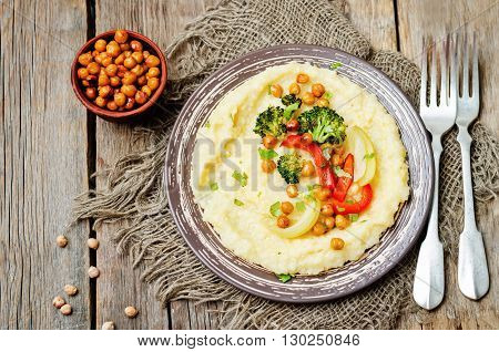 Polenta with roasted vegetables and chickpeas on a dark wood background.