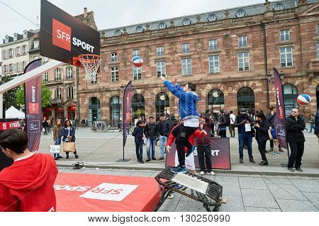 STRASBOURG FRANCE - MAY 14 2016: Young boy jumping to throw the basket ball in the center of Strasbourg during SFR Telecom presentation