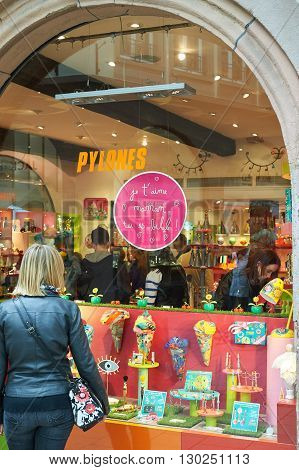 STRASBOURG FRANCE - MAY 14 2016: Woman admiring in windows store divers gifts and funny accesories during Mother Day - special sticker on glass say: I love you mom you're beautiful!